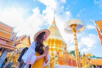 A young woman praying at Wat Phra That Doi Suthep, a famous tourist attraction and places of interest in Chiang Mai, Thailand