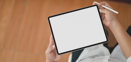 Cropped shot of view of man using blank screen digital tablet while sitting in his office room