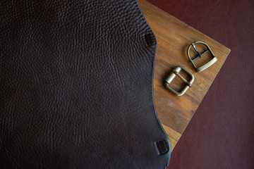 Leather working or Leather craft. Brown italian leather on leather craftman's work desk . Two buckle on wood background.