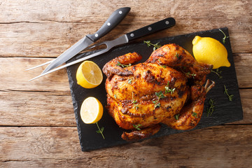 Traditional rotisserie chicken served with lemon closeup on a slate board on a table. Horizontal top view