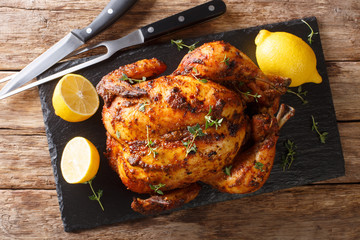 Homemade chicken rotisserie with thyme, lemon closeup on a slate board. Horizontal top view