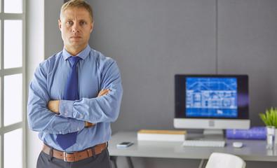 Happy businessman standing behind office desk, smiling