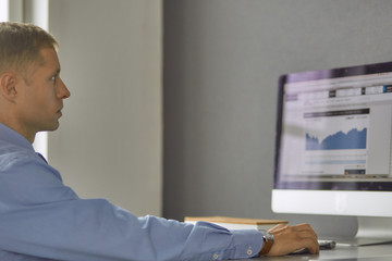 Young businessman working in office, sitting at desk, looking a