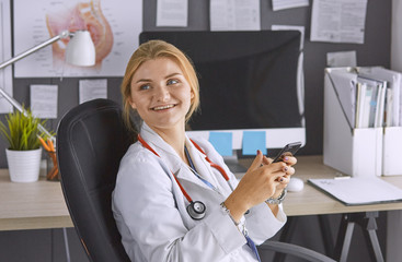 female doctor between patients in the office talking on the pho