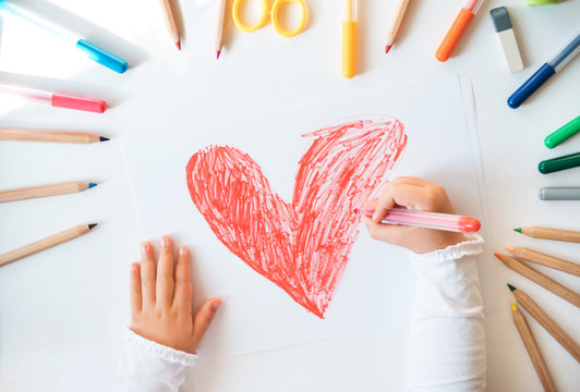 Close up of child's hands drawing red heart at white paper within colorful pens and pencils.