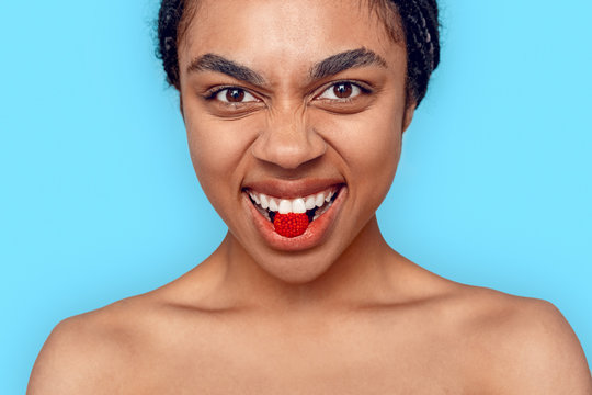 Beauty Concept. Young african woman isolated on blue biting raspberry smiling playful close-up