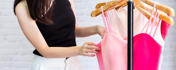 Banner of female holding hanger and touching elegant red dress while standing beside rack and examining clothes collection in showroom