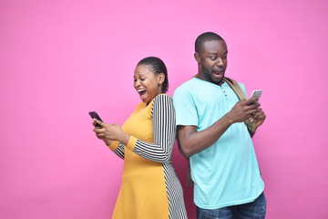 excited young black people standing back to back viewing contents on their phones, looking surprised, young african man and woman