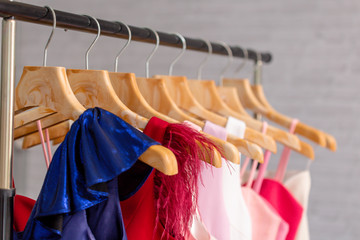 Beautiful blue and red dresses in composition with pink female clothes on hangers in modern showroom against blurred white wall