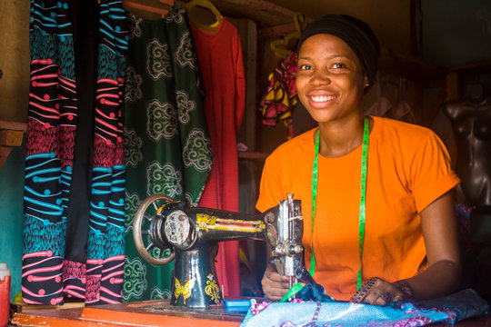 portrait of a pretty young african woman who is a tailor smiling