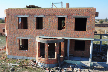 Brick house under construction. Luxury brick house wall construction with no roof.