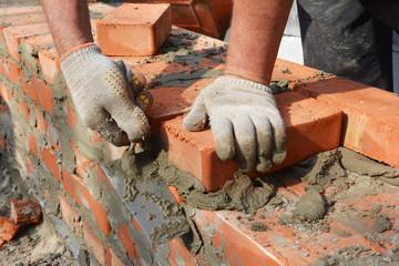 Bricklayer hands in masonry gloves bricklaying new house brick wall. Masonry close up.