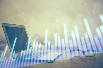 Stock market graph and table with computer background. Double exposure. Concept of financial...