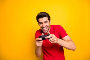 Portrait of cheerful guy play video games use joy stick want win winner in speed race wear stylish...