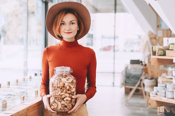 Woman holding glass jar with groceries in zero waste shop.