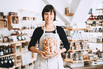 Owner or seller with glass jar of groceries in zero waste shop.