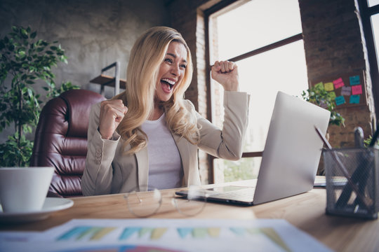 Photo of cheerful screaming entrepreneur seeing her corporation having taken first place in many charts feeling like champion after winning money awards