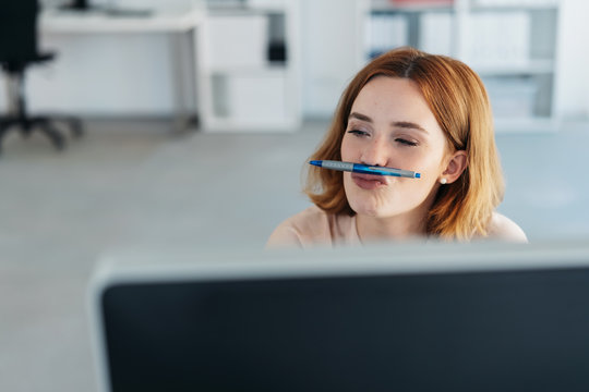 Playful young businesswoman with a pen mustache