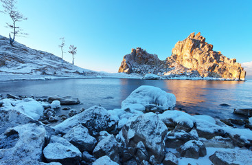 Baikal Lake in December. Olkhon island on a frosty clear morning. The famous Shamanka Rock is a natural landmark in the rays of the dawn sun. Magnificent winter landscape, natural background