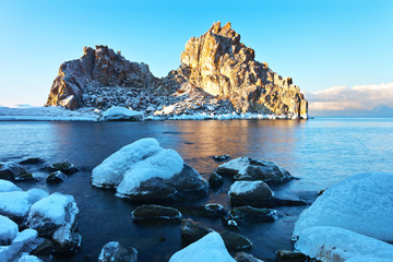 Baikal Lake in December. Olkhon Island on a frosty morning. Beautiful Shamanka Rock or Cape Burhan in the rays of the dawn sun. Magnificent winter landscape, natural background