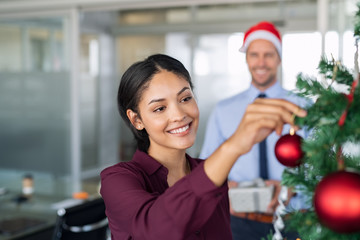 Businesswoman decorating christmas tree at office