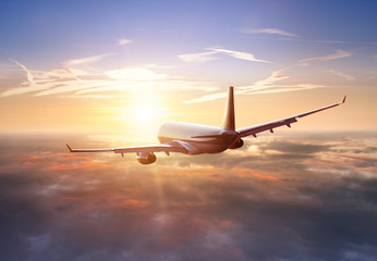 Poster Avion à Moteur Passengers commercial airplane flying above clouds in sunset light. Concept of fast travel, holidays and business.