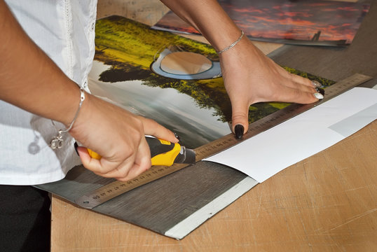 Manually crop photos. Knife and ruler on the table. Framing pictures with a stationery knife. Girl in a white shirt. Female assistant cuts photos. Woman prepares mockup of photos.