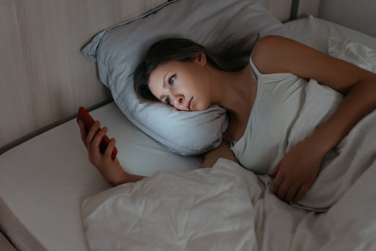 Young woman laying in bed and watching her smartphone at night. Insomia and unhealthy sleep because of phone and social networks dependence. Gadget concept