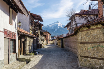 An old street in the mountain town of Bansko, now the largest mountain resort in Bulgaria. In the background the Todorka peak Wall mural