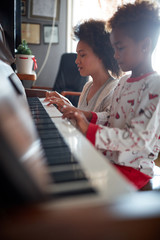 .Christmas, winter holidays, new year party and family concept. mother with child  play music on piano.