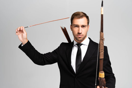 handsome businessman in suit holding bow and arrow isolated on grey