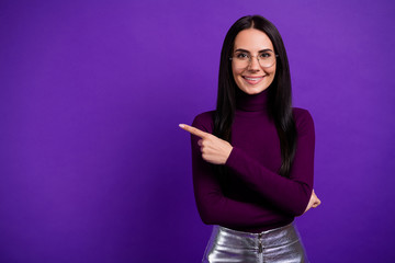 Photo of cheerful positive cute pretty charming girlfriend pointing into empty space isolated...