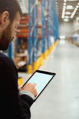Manager holding digital tablet in warehouse