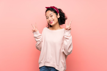 Asian young woman over isolated pink background showing victory sign with both hands
