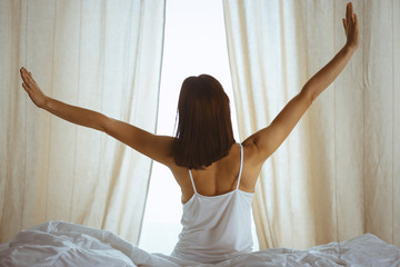 Woman stretching hands in bed after wake up, sun flare . Brunette entering a day happy and relaxed after good night sleep and back view. Concept of a new day and joyful weekend