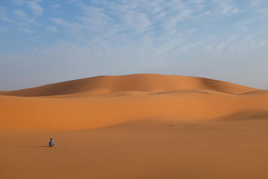 A man sitting quietly on a vast desert landscape doing meditation and relaxation