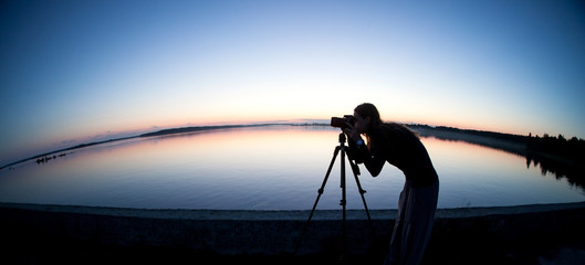 photographer takes a picture of evening landscape at sea