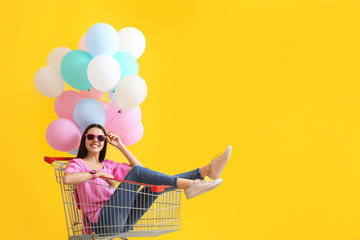 Young woman with shopping cart and balloons on color background