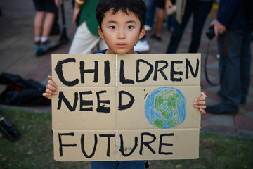 A child holds a placard during a 'drop dead' flashmob protest against climate change consequences at Lumpini Park in Bangkok