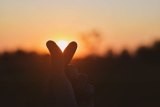 The person showing the symbol mini heart on the sunset background
