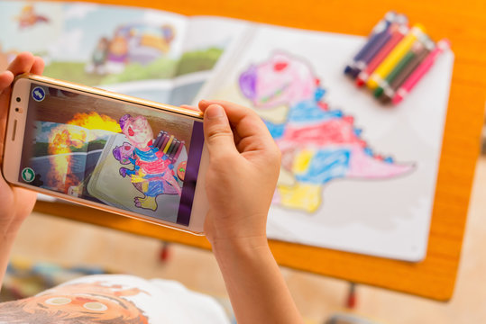 Zhongshan,China-August 8, 2017:kid playing Augmented Reality popup paintings of a filled dinosaur via mobile. AR and VR games become more and more popular.