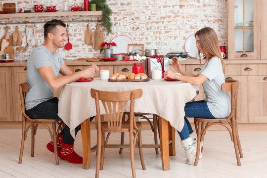 Happy young couple having breakfast on Christmas eve