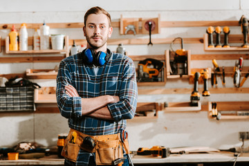 Fototapeta handsome carpenter in apron standing with crossed arms in workshop obraz