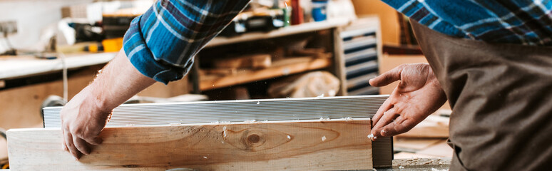 panoramic shot of woodworker holding plank near circular saw in carpentry shop