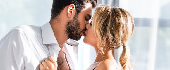 Business couple kissing while flirting in office, panoramic shot