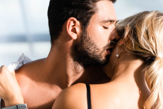Shirtless businessman kissing blonde colleague