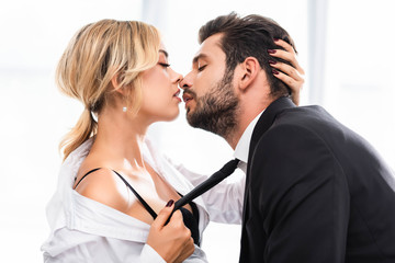 Side view of sexy businesswoman pulling colleague tie while flirting in office Fototapete