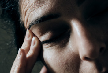 woman touching her forehead suffering from a headache or is stressed