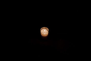 little single candle in the dark - hope concept .