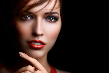 Close-up beautiful girl with bright evening party or prom make-up red lipstick isolated on a dark background